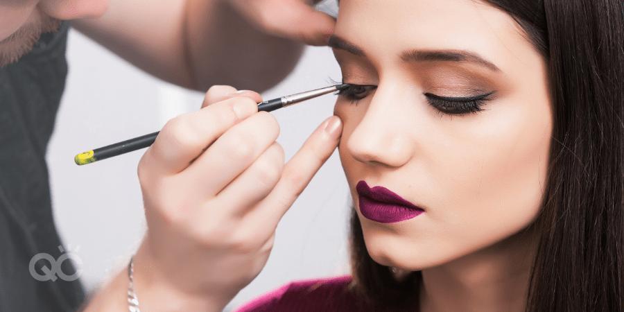 Makeup artist applying eye liner on female client