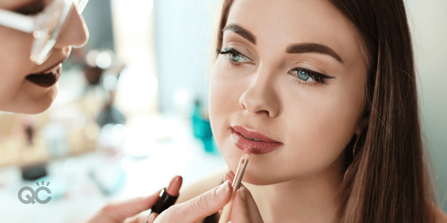 Makeup artist applying lip product to client