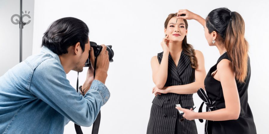 Photographer, makeup artist, and model on set of photoshoot