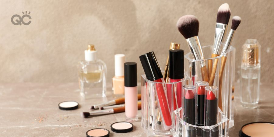 Lipstick holder with different makeup products on table against color background.