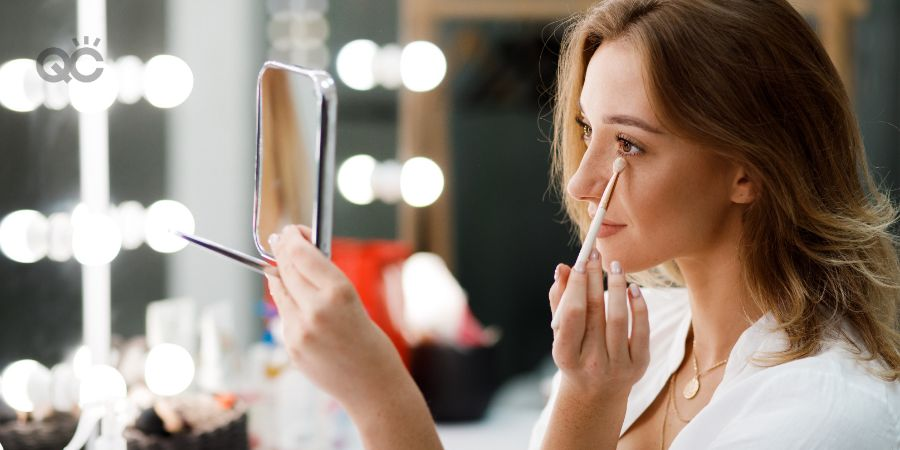 Makeup career article, last in-post image, woman applying makeup to her own face at home