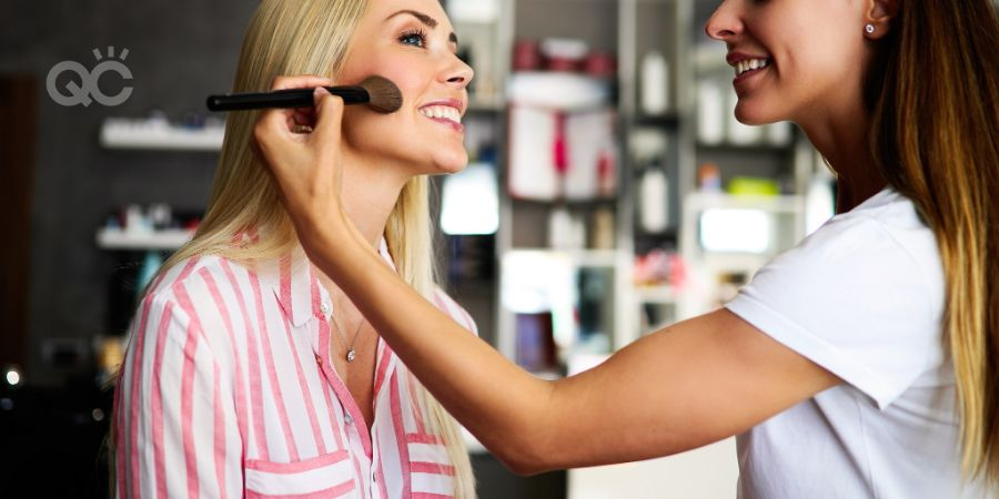 Makeup artist applying liquid tonal foundation on the face of the woman in make up room