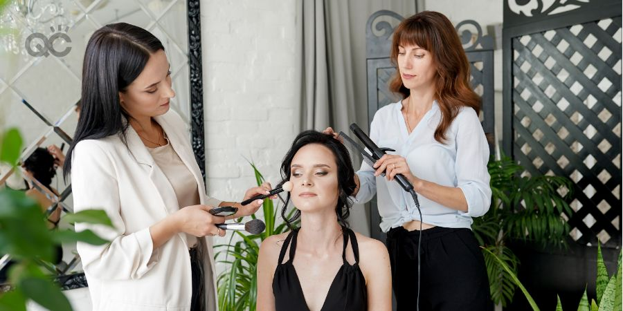 Makeup and hairstyle process with beautiful young woman in modern interior room with green plants