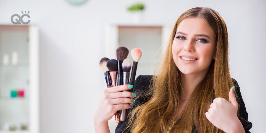 Happy woman holding up makeup brushes and giving thumbs up