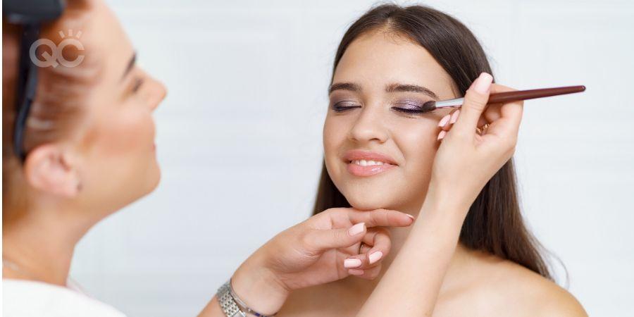 Makeup artist applying eyeshadow on model's eyelids