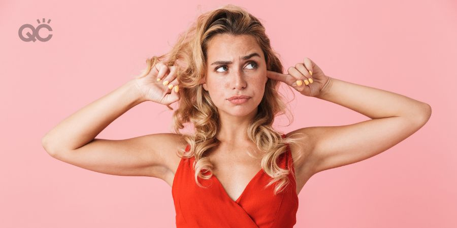 Image of a displeased young pretty blonde cute woman in dress posing isolated over pink wall background covering ears because of loud.