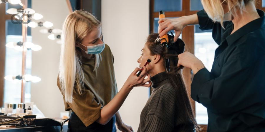 Makeup artist and hair stylist working on client at the same time in salon