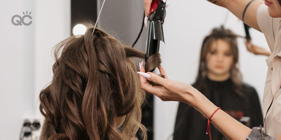 Hair stylist curling client's hair at salon