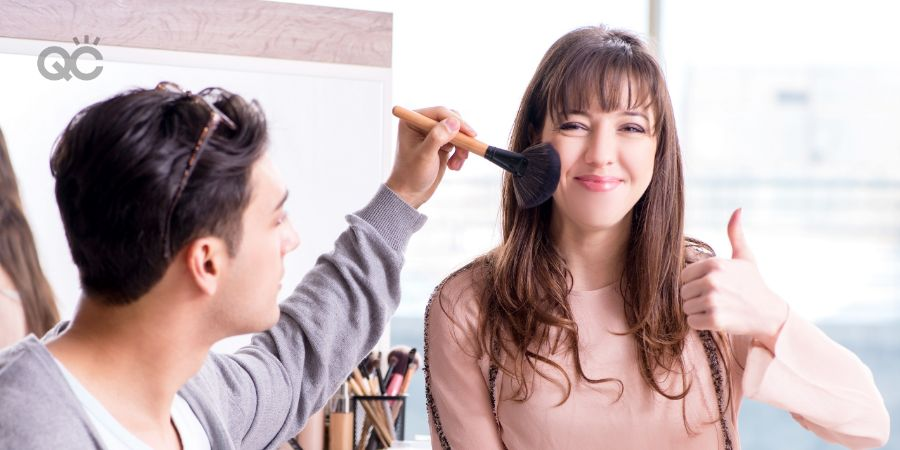 Man doing makeup on female client in beauty salon
