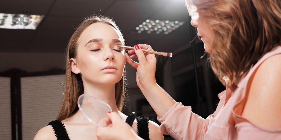 makeup artist appling a primer on an eyelid of a young beautiful woman using a brush before dabbing eyeshadows. concept of professional make up training
