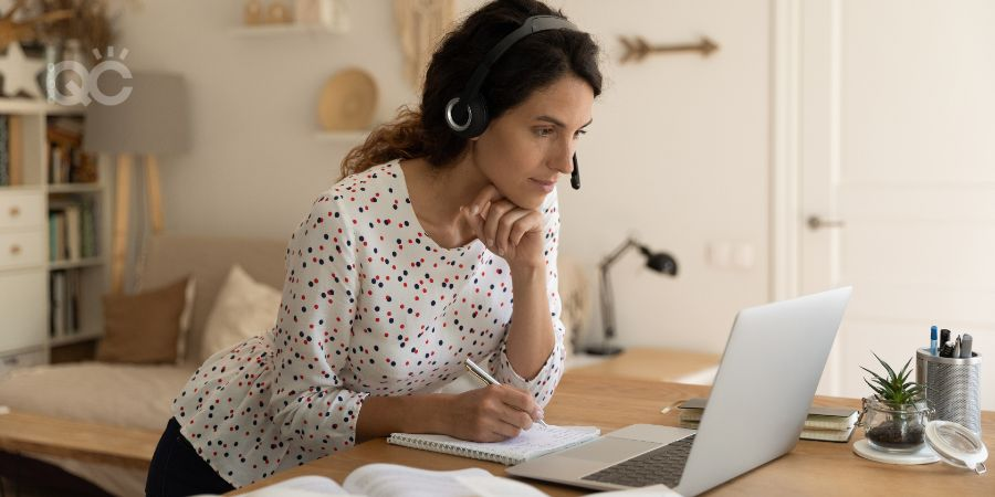 Woman standing at counter, writing in notebook while watching video on laptop at home